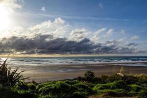 Waves and black sand highlight a visit to the beach. Taranaki, Beach, Taranaki, New Zealand photo