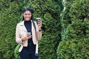 happy african american woman on the street with coffee photo