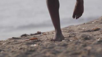 een jonge mans blote voeten lopen op het strand. video