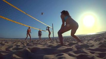 POV of a girl passing while playing womens beach volleyball video
