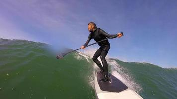 POV of a man who cant get a grip on his paddle while surfing on his sup paddleboarding video