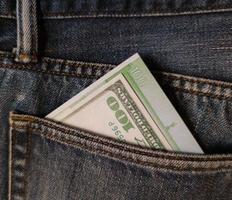 Cien dólares y cien euros en el bolsillo trasero de los vaqueros. foto