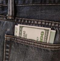 dólares y euros en el bolsillo de los pantalones vaqueros foto