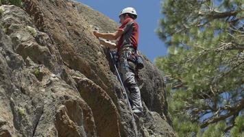 A young man rock climbing on a mountain. video