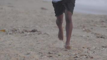 A young mans barefoot feet running on the beach. video