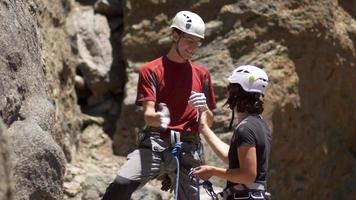 A couple celebrating and slapping hands giving a high five while rock climbing. video
