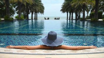 Young Asian woman enjoying outdoor swimming pool video