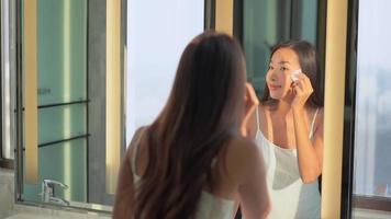 jovem asiática limpando o rosto enquanto se olha no espelho video