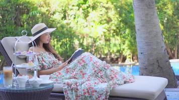 Young asian woman reading a book by the pool video