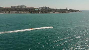 A white yacht with a sail floats in the blue sea in summer Aerial shot video