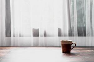 A glass of water and a coffee mug are at the desk. photo