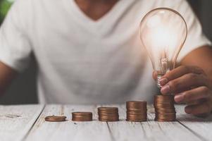 businessman holding lightbulb money stack idea saving energy and accounting finance 3D illustration photo