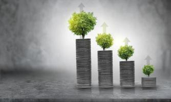 Creciente crecimiento empresarial y cultivo financiero de plantas a partir de monedas en botellas de vidrio sobre fondo verde foto