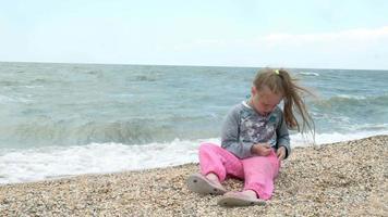 petite fille sur la plage de la mer recueille des coquillages été video
