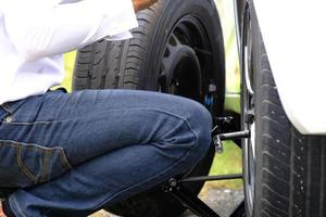 Joven asiático sentado en un automóvil roto pidiendo ayuda y reparando vehículos con ruedas en la carretera, reemplazando neumáticos de invierno y verano. concepto de reemplazo de llantas estacionales foto