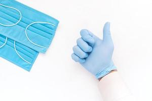 Mano en guantes médicos mostrando un pulgar hacia arriba sobre fondo blanco. foto