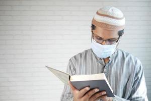 Hombre musulmán con mascarilla leyendo holly libro del Corán interior foto