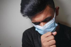young sick man coughing and sneezes against white wall photo