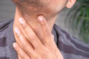 Hombre no reconocido que sufre de dolor de garganta de cerca foto