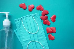 Surgical masks with heart shape and hand sanitizer on color background photo