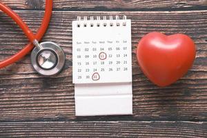 Estetoscopio, calendario y símbolo de forma de corazón en la mesa foto