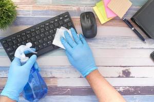 Mano en guantes de goma azul y teclado desinfectante de tejido blanco foto