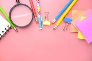 magnifying glass and stationery on pink photo