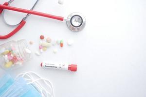 corona virus blood test tube and medical pills on white background photo