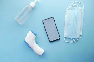 flat composition of smart phone, mask, thermometer and sanitizer on table photo