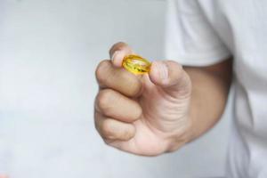 mano que sostiene el suplemento de aceite de pescado de cerca foto