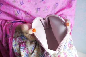 mano de mujer abre una billetera vacía sobre fondo rosa foto