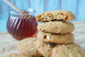 Pila de galletas integrales y miel sobre fondo de madera foto