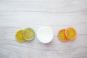 top view of petroleum jelly in a container and slice of lemon on table photo