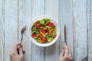 women hand with knife and fork eating fresh vegetable salad bowl on table, photo