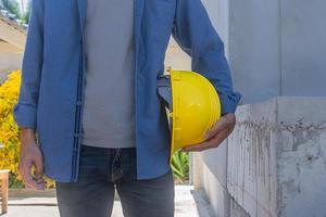 Ingeniero arquitecto arquitecto sosteniendo casco casco trabajando en la construcción del sitio foto