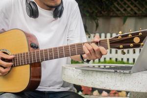 hombre tocando la guitarra y aprendiendo clase de guitarra en línea foto