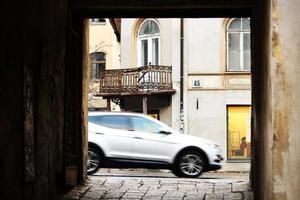 Puerta de la ciudad vieja con calle visible y coche gris foto