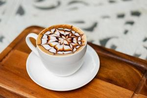 Hot latte art coffee on wood table, relax time photo