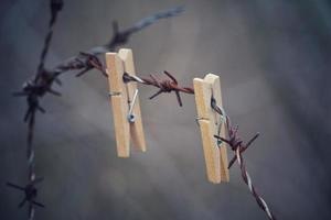 Pinza de madera en la valla de alambre de púas foto