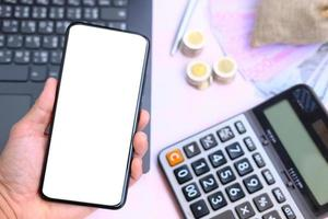Hand holding smartphone with money on the table and work space, business and technology concept photo