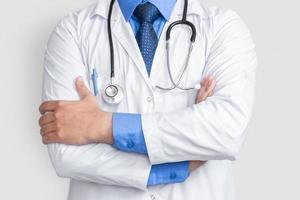 Varón joven médico cruzar el brazo sobre antecedentes aislados, concepto de salud foto