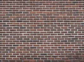 Dark red brick wall as a background texture photo