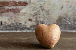 Patata roja en forma de corazón sobre fondo vintage foto