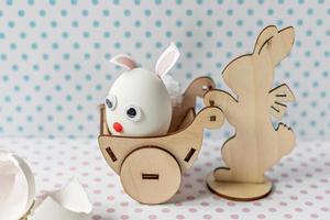 Wooden rabbit carrying a cart with an egg with bunny ears and a muzzle photo