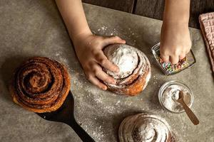 Children's hands in the frame sprinkle a fresh baked bun with cinnamon photo