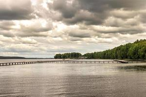 Wooden pier on the lake at sunset before the rain in summer photo