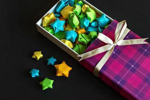 Colored gift box with satin bow with origami paper stars on black background photo