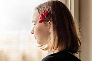 Portrait of a beautiful happy girl looking out the window with hope and expectation photo