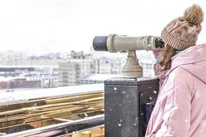 A young girl looks through coin-operated binoculars on the observation deck overlooking the city photo