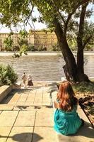 Mujer joven con un vestido verde se sienta con la espalda opuesta al terraplén del río foto